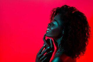 Lächelnde Frau vor neonfarbigen Hintergrund.